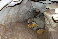 Caver Crawling Through Honeycomb Hill Cave